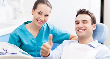 Man in dental chair smiling and giving thumbs up