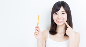 Woman holding toothbrush and pointing to her smile