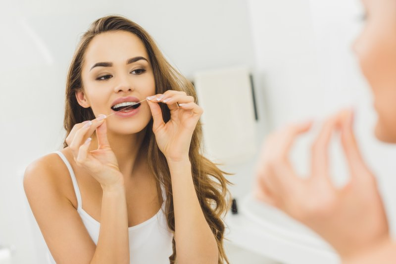 Woman looking in the mirror while flossing